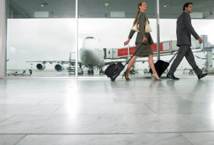 Businessman and woman walking through airport, ground view